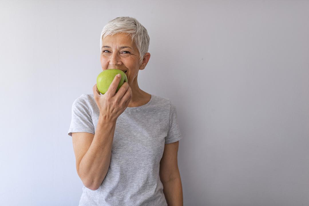 Femme mangeant une pomme verte ©iStock